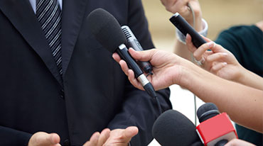 Man in suit being interviewed by reporters with microphones