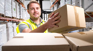 A young man unloading boxes from a truck into a warehouse