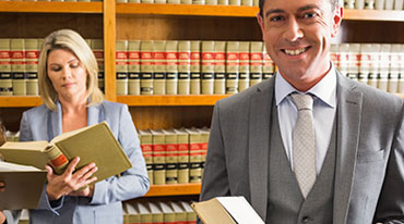A male and a female attorney in a law library reading books of statutes