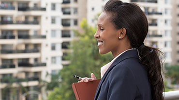 Woman standing on balcony holding a folder looking at commercial property