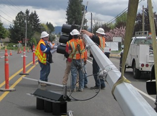 Crews works to mount a new traffic signal to the mast arm