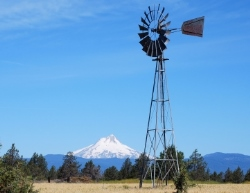 A windmill faces north with a view of Mt. Hood to the east against blue skies