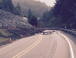 Landslide covers entire left lane of a two-lane road. The right hand lane is left badly damaged.