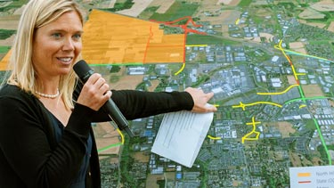 Speaker pointing at map with funding projects outlined