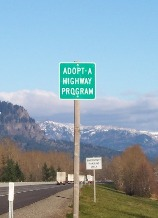 A green Adopt-A-Highway sign on the right side of a road