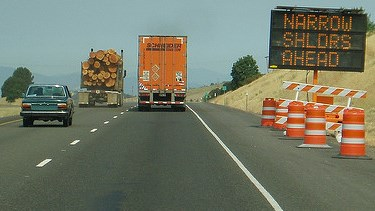 Reader board sign and orange barrels on the highway right of way warn motorists of upcoming work zone on I-5.