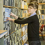 woman reaching for books on a library bookshelf