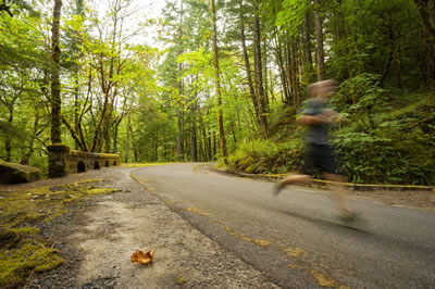 Boy running along the Historic Highway State Trail with green trees.