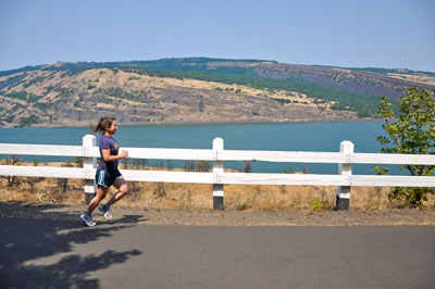 Girl jogging next to the iconic white fence with view of the Columbia River in the back.