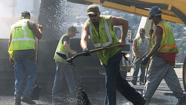 Construction workers shoveling asphalt