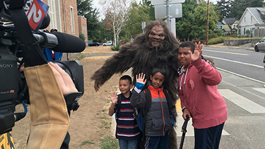 Photo of kids and a man dressed as sasquatch waving to a tv camera