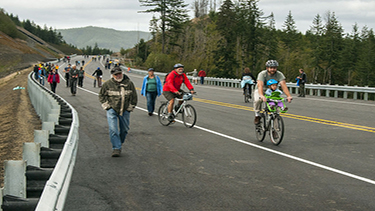 Photo of a group of people riding bicycles along a highway