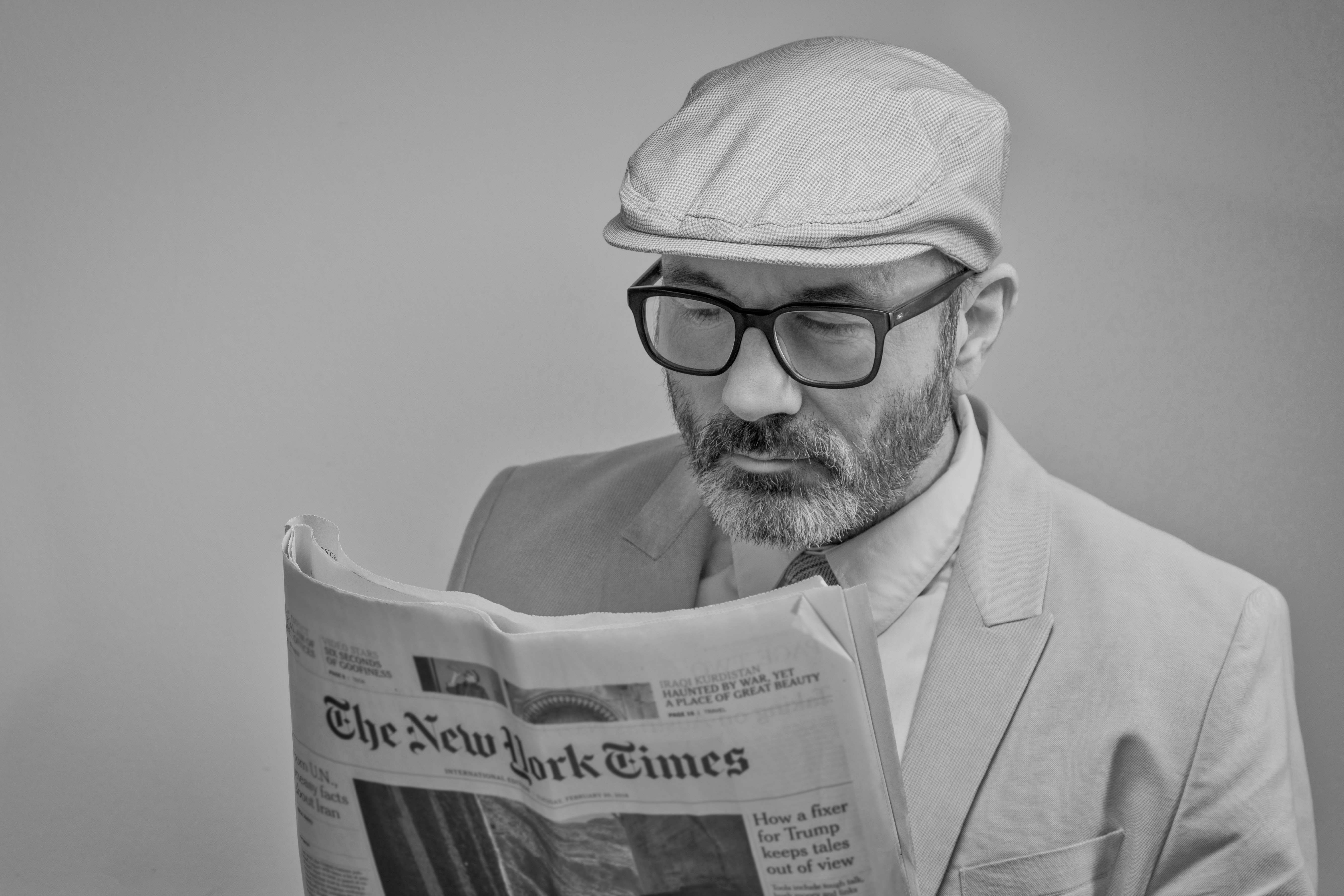Man with glasses reading a newspaper