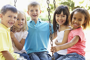 Smiling group of young kids on a swing