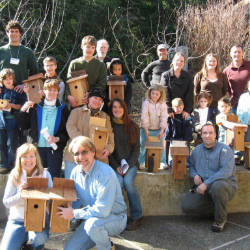 Photo from bat house workshop of people holding bat houses