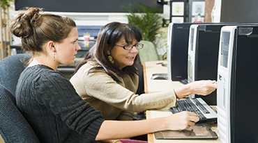 Female providing computer assistance to young female