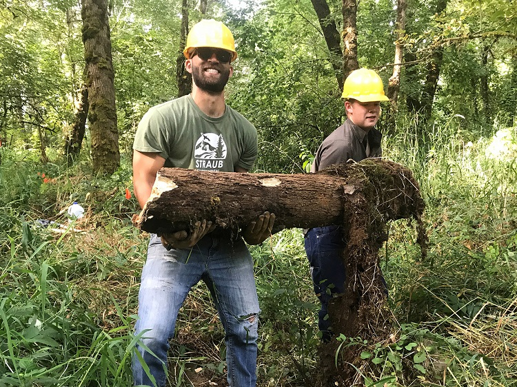 2 people carrying a log doing fieldwork