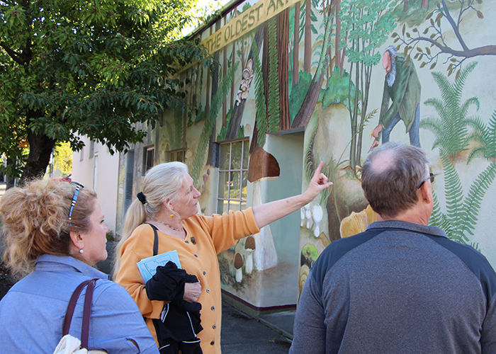 Three people look at a mural in downtown Estacada Oregon