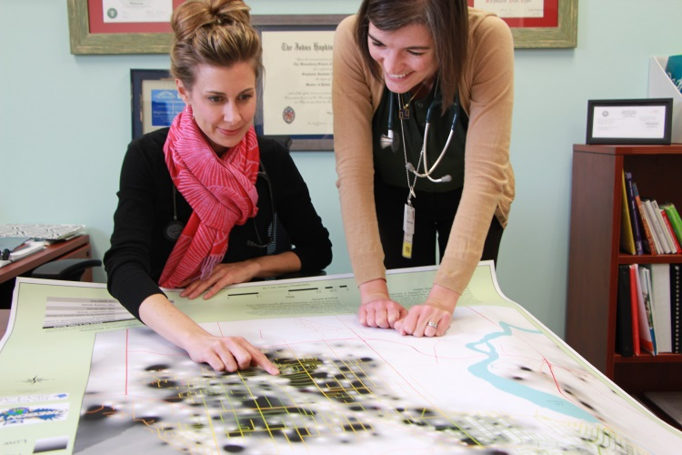 Two women view and point to a place on a large paper map spread across a table.
