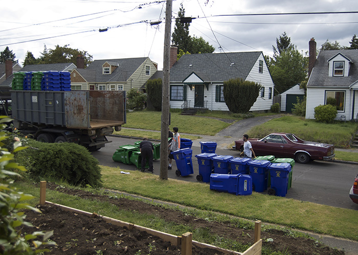 Sanitation workers drop off garbage and recycling buckets.