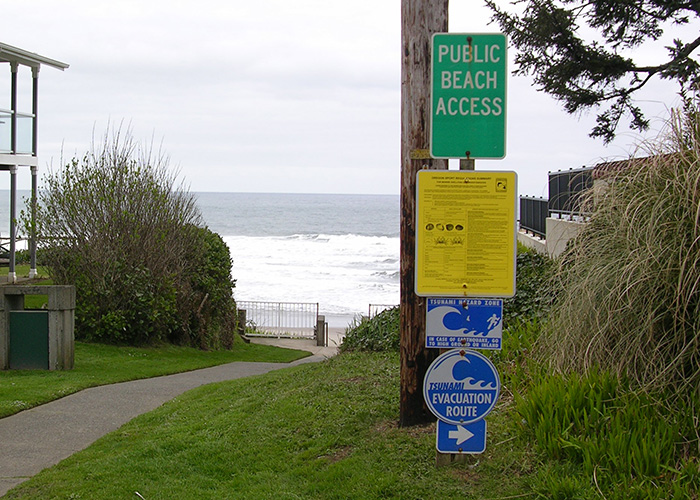 A sign by a beach path includes tsunami warnings and points towards an evacuation route