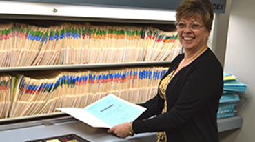 Employee standing in front a shelf of file folders.