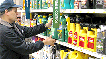 Man inspecting a fertilizer bottle on a shelf.