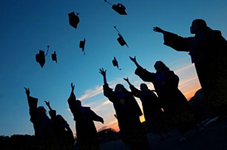 Students throwing their graduation caps into the air. It leads to the Learning Options page.