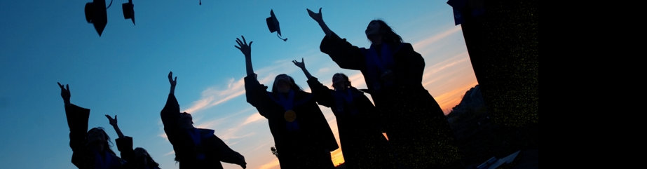 image of graduates throwing caps in the air