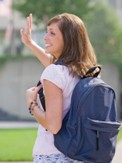 High school girl waving with backpack