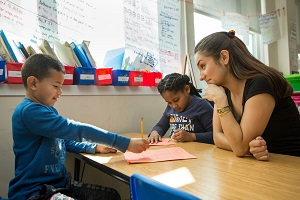 Teacher helping two second grade students
