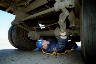 ODOT employee inspecting the under carriage of a truck