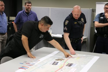 An employee and a police officer discuss and pointing at a map.