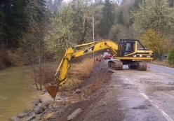 An excavator works to repair and shore up a roadside that has eroded.