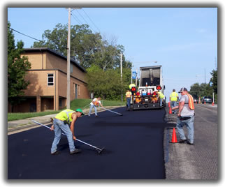 a highway maintenance crew smoothing a newly paved road