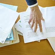 Hand pointing to paper on desk