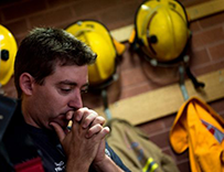 Man in what appears to be a fire station, anxiously holding his folded hands against his mouth and nose