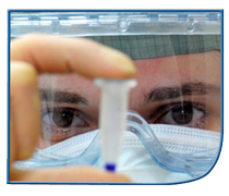 Image of a person wearing protective goggles and face mask examining a test specimen