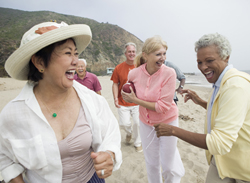 Group of active older adults laughing and playing on a beach