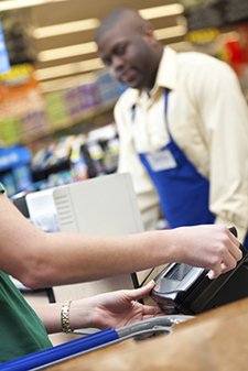 grocery cashier ringing up purchase while shopper swipes eWIC card