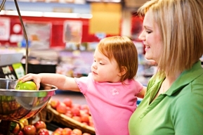 mother and toddler daughter weighing produce in a grocery store