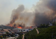 Houses in a valley, behind them on a hillside fire is visible with heavy clouds of smoke overhead