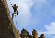 Rock climber ascending a steep cliff