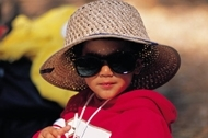 Child sitting in sun wearing oversized sunglasses and straw hat