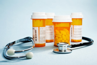 Four prescription medication bottles containing pills and a stethoscope