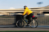 Man riding a bike, with blur indicating movement