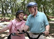 Two seniors, a man and a woman, wearing helmets and sitting on bikes in a park setting