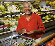 Smiling man pushing a shopping cart in the produce section of the grocery store