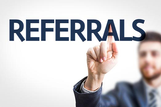 Man with text on a screen that says Referrals