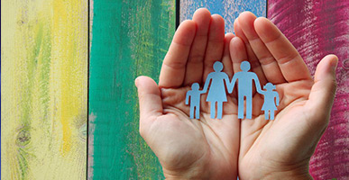 Paper family in hands on a wooden colored background welfare concept